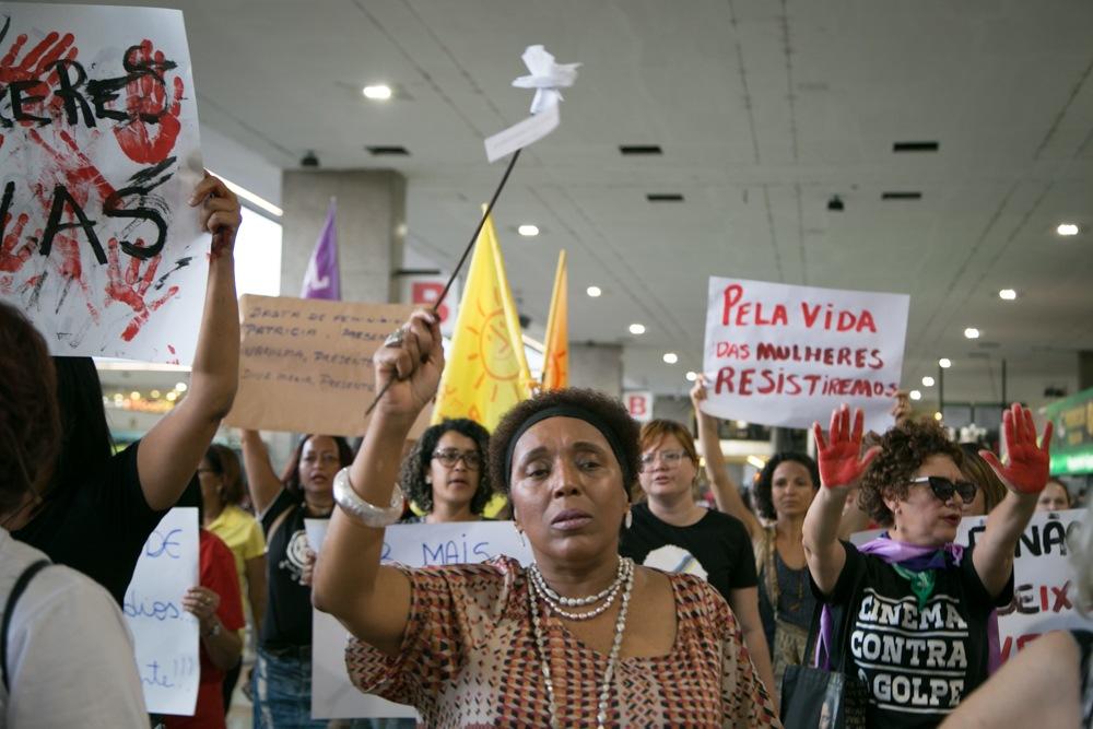 """Foto de manifestação, com uma mulher negra à frente segurando uma flor branca de papel, sendo seguida por outras mulheres segurando cartazes com dizeres """"pela vida das mulheres"""""""