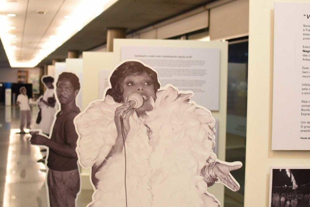 Imagem de um totem da exposição, com foto de uma mulher negra envolta em plumas cantando ao microfone.