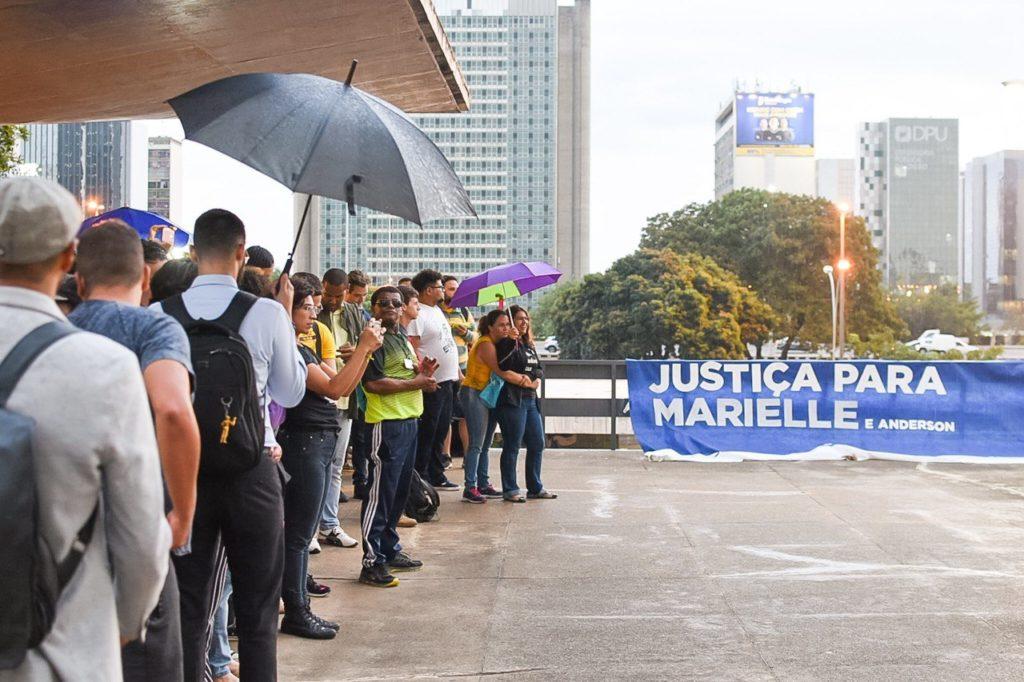 Pessoas sob a marquise e faixa com os dizeres Justiça para Marielle